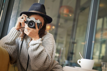 Beautiful brunette in modern cafe with vintage camera