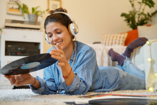 Attractive brunette listening to vinyl records on floor at home