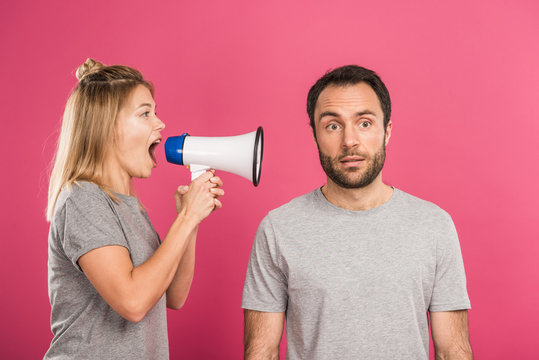 angry woman yelling with megaphone at man, isolated on pink