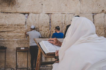 Religious orthodox jew praying at the Western wall and reads the Torah in Jerusalem old city