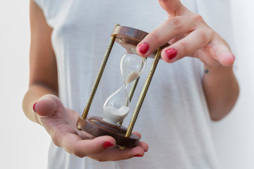 Woman's hands holidng an hourglass