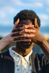 Hands covering eyes of a young black man