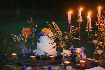 Wedding cake on table with candles outdoors