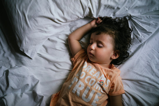 Baby girl sleeping on bed with t-shirt message 'Dreams do come true'