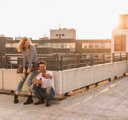 Young couple relaxing on roof terrace at sunset taking selfie with cell phone