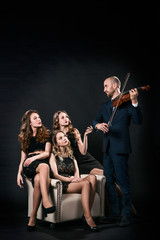 Three beautiful girls in black evening dresses are sitting in the chair, and the man plays the violin