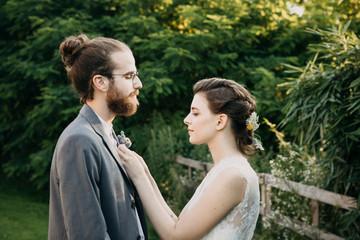 Bride adjusting groom's suit outdoors