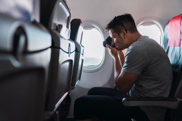 Man taking a picture in airplane