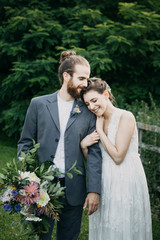 Happy affectionate bride and groom standing on a meadow