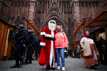 French police patrol outside the Strasbourg Cathedral as a man dressed as Father Christmas poses with a tourist
