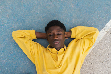 Young black man sleeping on floor, with hands behind head
