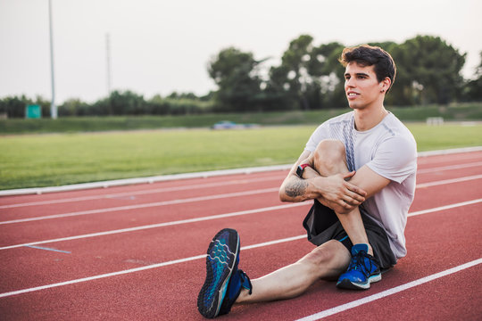 Athlete doing exercises on tartan track