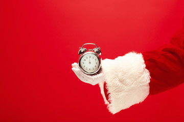Santa holding an old alarm clock on red background. The season, winter, holiday, celebration, gift concept