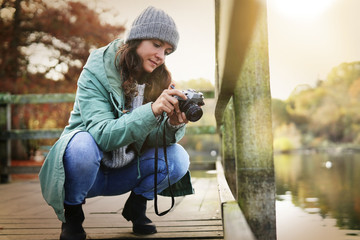Attractive brunette winding vintage camera outdoors in fall