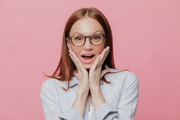 Human facial expressions, reaction concept. Beautiful prosperous business lady keeps both hands on cheeks, wears elegant white striped shirt, has surprised facial expression, isolated over pink wall
