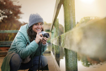 Attractive brunette taking photos outdoors in fall