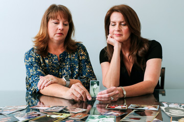Cady Evans and her sister Crystal Deckard hold an old photograph as they reminisce on the loss of their mother in California