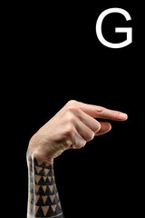 tattooed hand showing latin letter - G, sign language, isolated on black