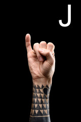 cropped view of tattooed hand showing latin letter - J, sign language, isolated on black
