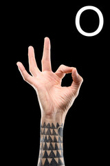 partial view of tattooed male hand showing cyrillic letter, deaf and dumb language, isolated on black