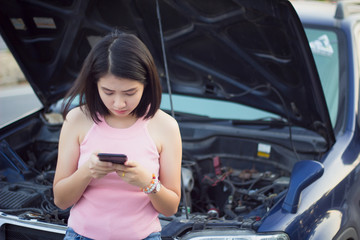 Young woman standing by broken car on the road and using smartphone calling assistance.