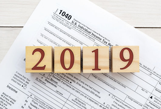 Wooden cubes with numbers 2019 on tax form.