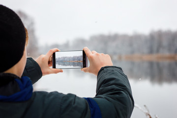 the guy takes pictures on the phone winter nature, hands taking pictures of winter nature, Hiking, the concept of winter recreation