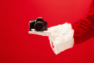 The hand of santa claus holding a camera on red background. The season, winter, holiday, celebration, gift concept