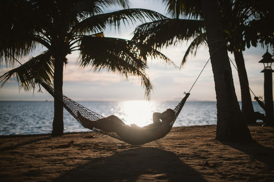 A young man is lying in a hammock at sunset by the ocean. Handsome guy is resting in a hammock among palm trees on the seashore.