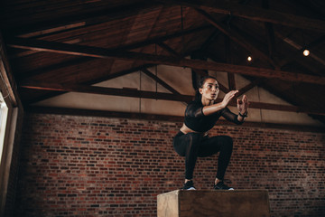 Sports woman doing a box jump at the gym