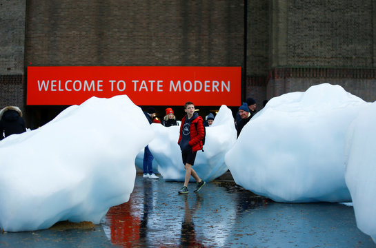 Visitors walk around Ice Watch, a piece of installation art made up of giant blocks of ice by artist Olafur Eliasson, at Tate Modern in London
