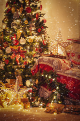 Living room, decorated fireplace with wood mantelpiece, lit Christmas tree with baubles, stars, pine cones, cosy armchair with read throw, wooden ornaments, wreath, created snow, selective focus