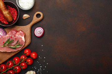 Pieces of raw pork steak on cutting board with cherry tomatoes, rosemary, garlic, red pepper, onion, salt and spice mortar on rusty brown background