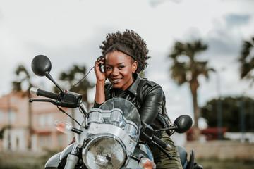 Cheerful black woman on motorbike
