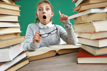 Schoolgirl having good idea, pointing finger up. Photo of astonished young girl around books. Education concept