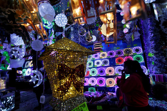 A girl is silhouetted as she stands at a market stall selling Christmas lights in Monterrey