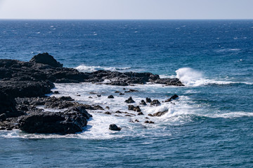 Waves breaking over the edge of the lava field volcanic rocks at Puerto de Naos, La Palma, Canary Islands