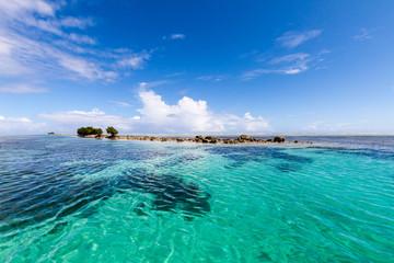 Azure turquoise blue lagoon, small uninhabited reef island motu full of dangerous rocks and some mangroves trees. Pohnpei island, Micronesia, Oceania.