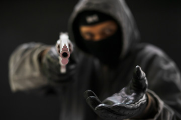 Robber with a gun robbing intimidate.Crime and robbery concept.