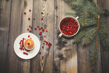 A light gray wooden tabletop on which lie fresh spruce branches with a cup of fresh berries a red white plate with a fresh baked muffin decorated with red berries and powdered sugar.