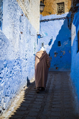 A man with a traditional dress is walking in the beautiful blue medina of Chefchaouen, Morocco.