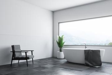 White bathroom corner tub and armchair