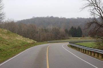 A empty curved road in the countryside on a cloudy day.