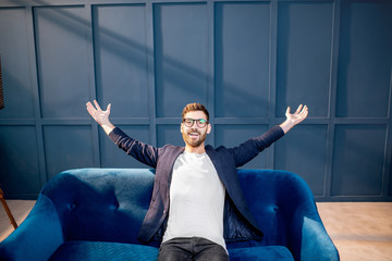 Portrait of relaxed businessman dressed casualy sitting on the couch on the blue wall background indoors