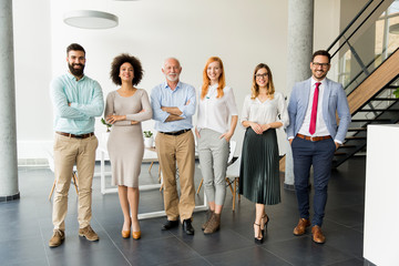 Line of happy and positive business people standing in the office