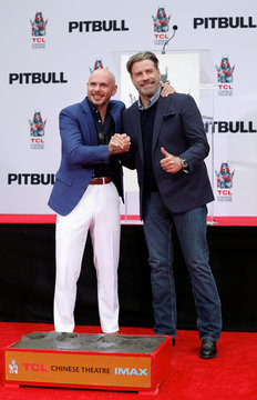 American rapper Pitbull places his footprints in cement during a ceremony in the forecourt of the TCL Chinese theatre in Los Angeles