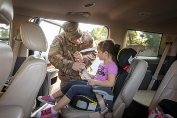 Soldier helping his daughter with her car seat