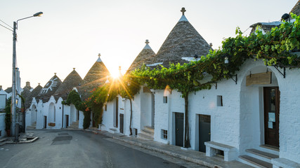 Wall Mural - Trulli houses in Alberobello city at sunset time,  Apulia, Italy