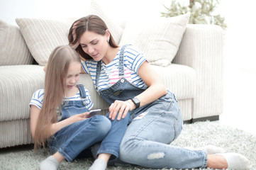 mother and her little daughter use a smartphone to view the photo