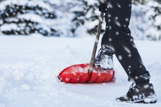 Public service worker or citizen shoveling snow during heavy winter blizzard